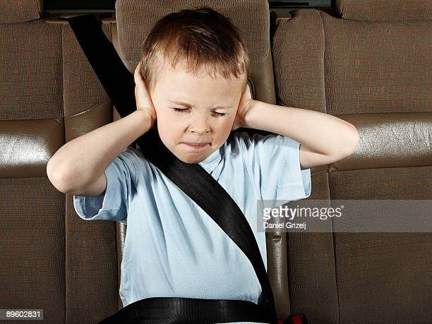 Boy in car with eyes closed, hands covering ears