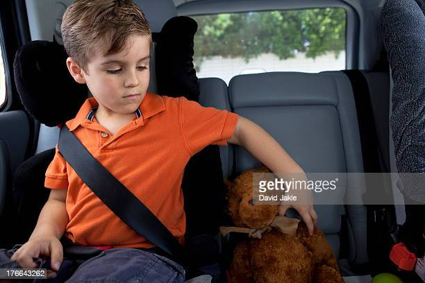 Boy in child safety seat in car with teddy bear