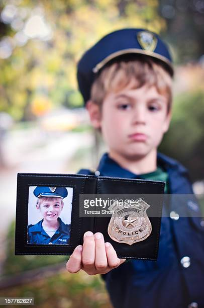Boy in Costume Holds Police Badge