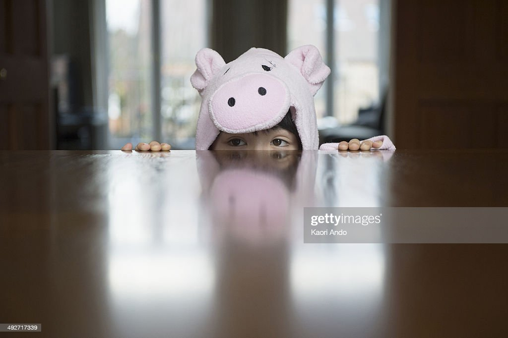 Boy in costume peering over table : Stock Photo