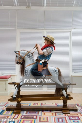 Horse Toys For Boys : Boy in cowboy costume riding toy horse stock photo getty