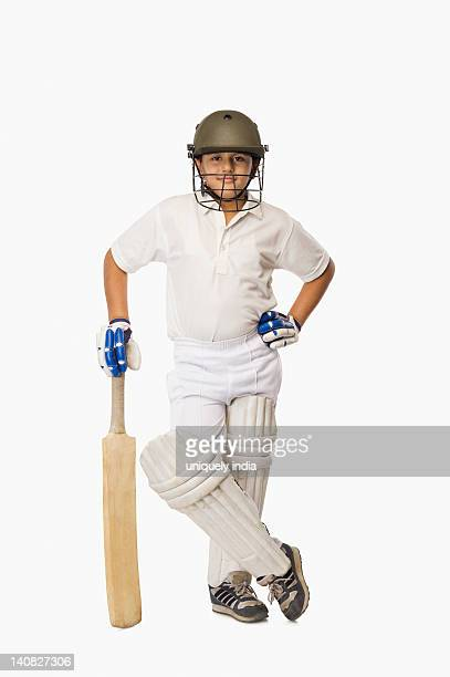 Boy in cricket uniform holding a cricket bat