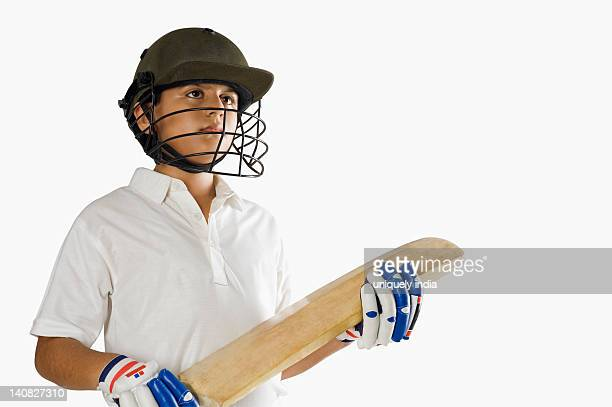Boy in cricket uniform holding a cricket bat