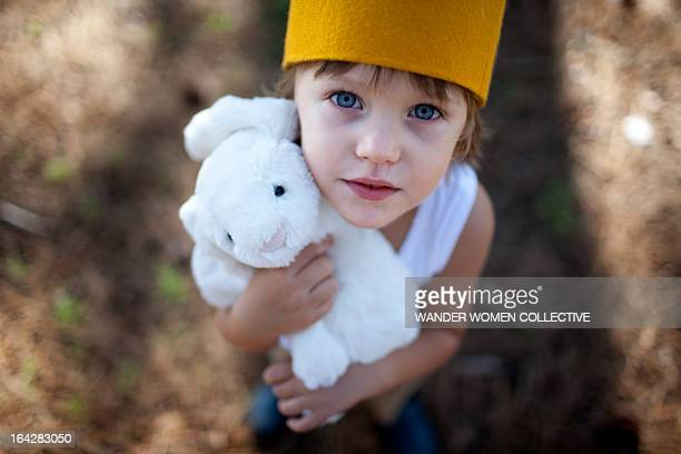 Boy in crown holding stuffed toy bunny rabbit