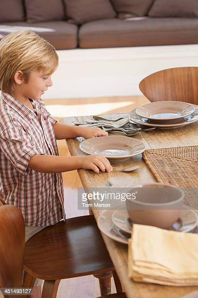 Boy in dining room setting table