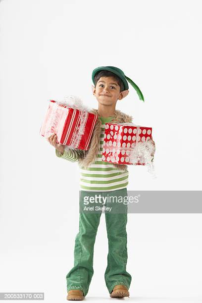 Boy (6-7) in dressed as an elf, holding Christmas gift