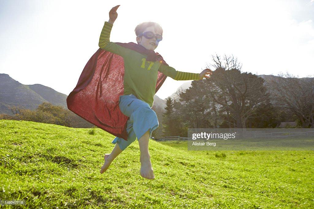 Boy in fancy dress jumping down a hil : Stock Photo