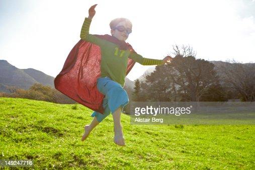 Boy in fancy dress jumping down a hil