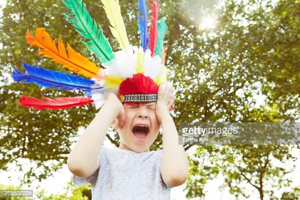 Boy in feather headdress screaming in garden