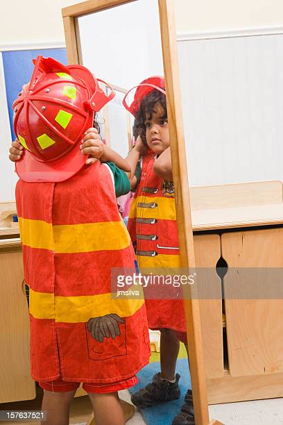 Boy in firefighter costume looking in full length mirror