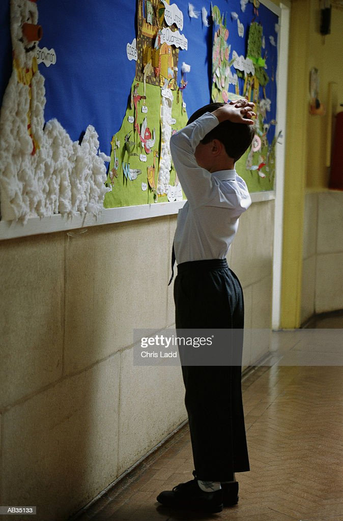 Boy (7-9) in front of collage on wall in school corridor, profile, hands on head, detention, punishment