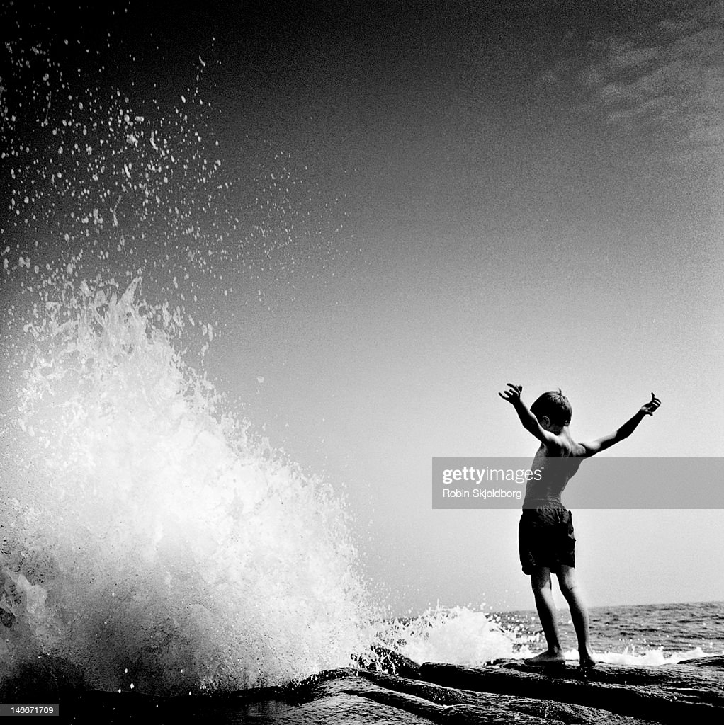 Boy in front of wave.