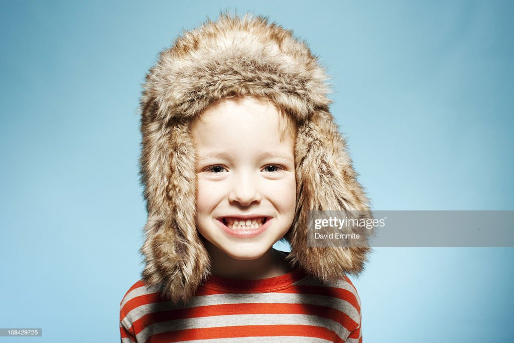 Boy  in fur hat against blue background : Stock Photo
