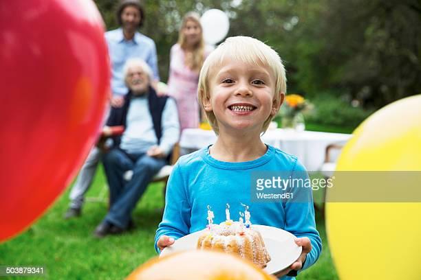 Boy in garden holding birthday cake