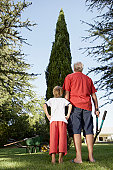 Boy (7-9) in garden with grandfather, looking at tree, rear view