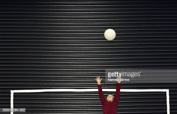 Boy (6-8) in goal reaching for football