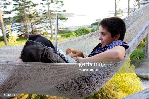 Boy in hammock using laptop computer : Foto de stock