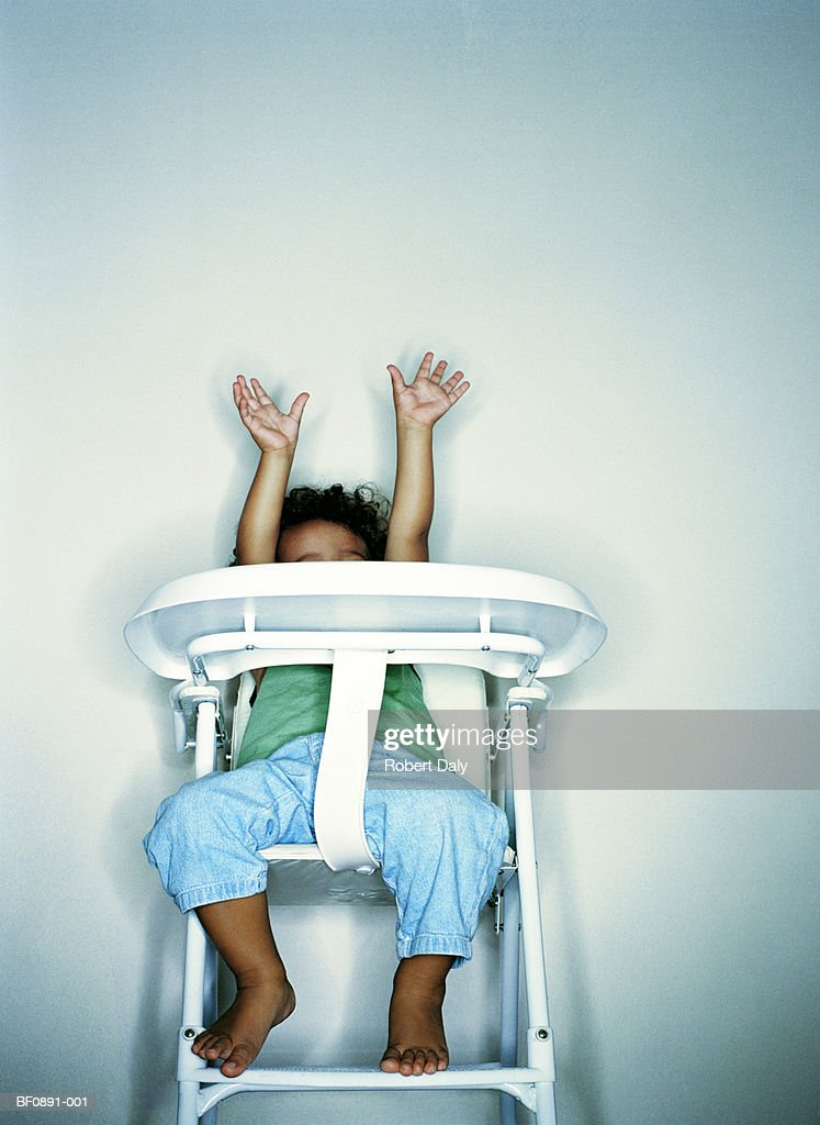 Boy (21-24 months) in highchair, arms raised, low angle view : Stock Photo