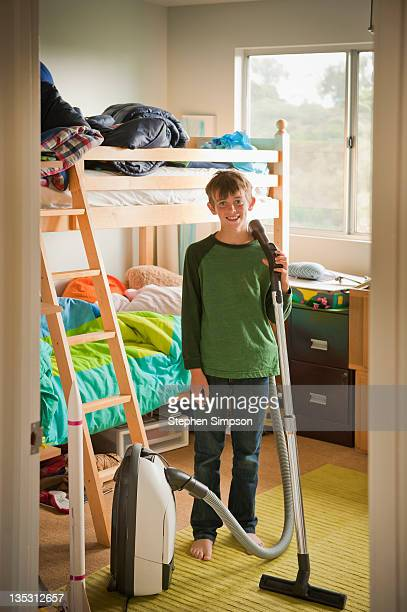 boy in his bedroom with vacuum cleaner