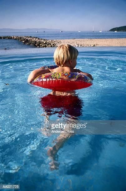 Boy (2-4) in inflatable ring in pool overlooking ocean, rear view