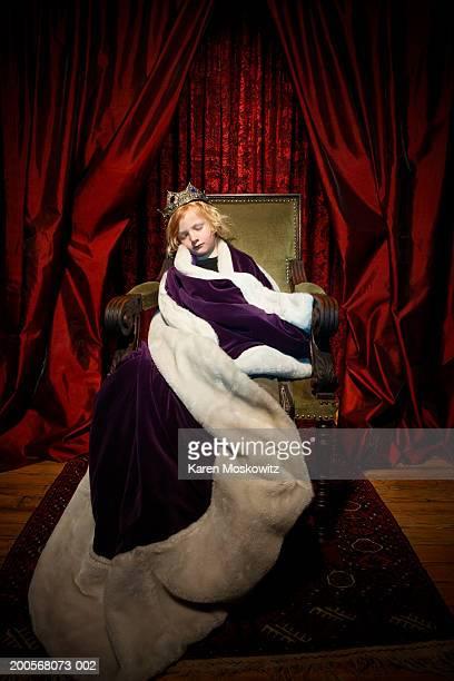 Boy (4-7) in king's costume sleeping in throne