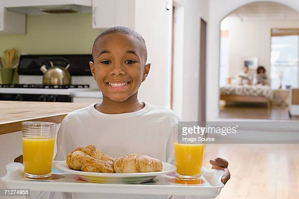 Boy in kitchen carrying breakfast on tray