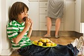 Boy in kitchen eating cupcakes