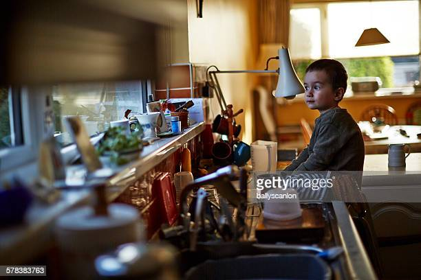 Boy in kitchen, looking out window