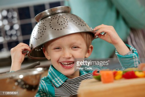 boy in kitchen with cullender on his head : Stock Photo