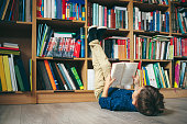 Boy laying on the floor with the feet up, reading a book against multi colored bookshelf in library. Education, Knowledge, Bookstore, Lecture. Pupil holds a book in his hands.