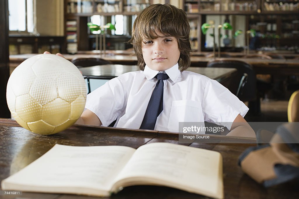 Boy in library with football
