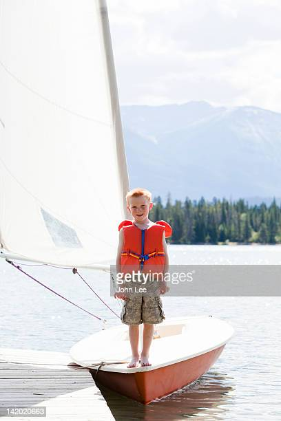 Boy in life jacket standing on sailboat
