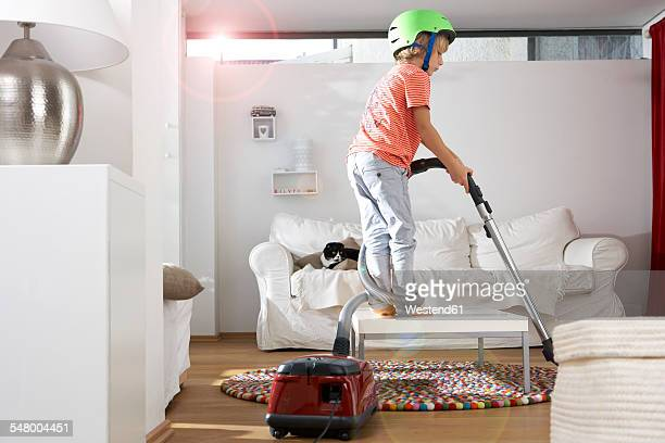 Boy in living room hoovering