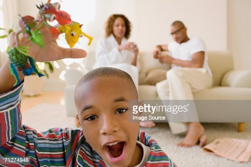 Boy in living room playing with monster finger puppets : Bildbanksbilder