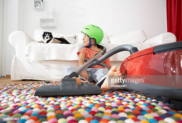Boy in living room with cat and vacuum cleaner