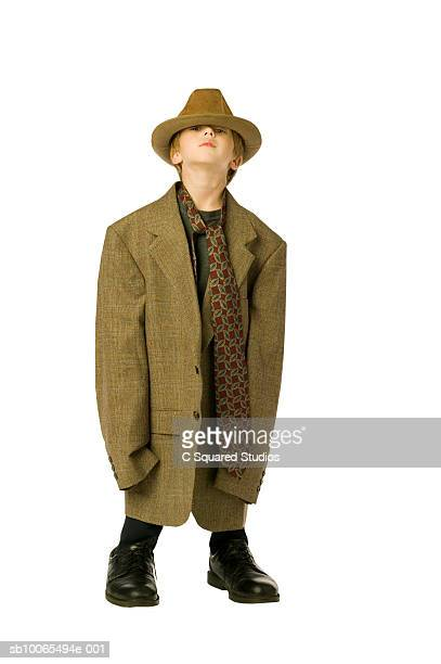 Boy (4-5) in man's clothes peering up under oversized hat, portrait