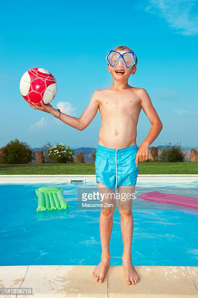Boy in mask playing by swimming pool
