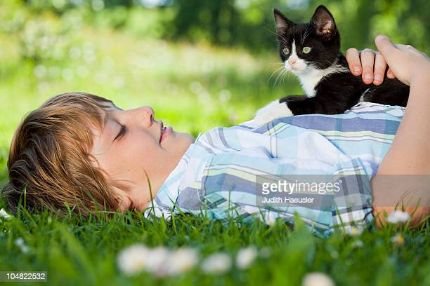 Boy in meadow hugging a cat