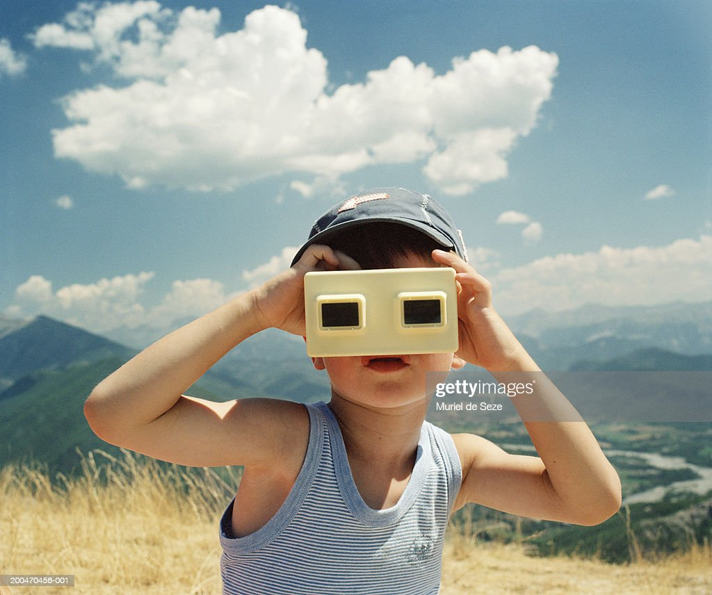Boy (5-7) in mountainous landscape using slide viewer : Stock Photo
