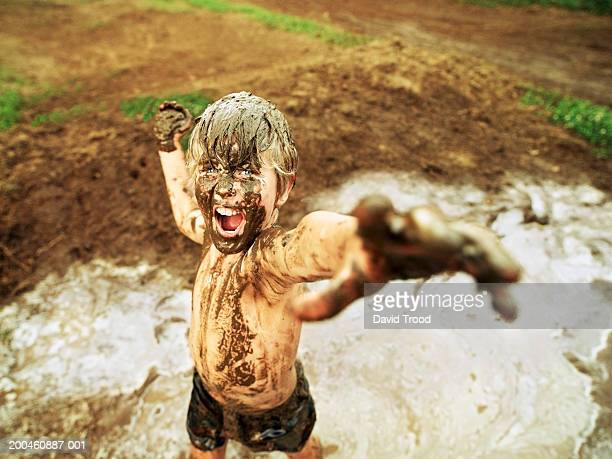Boy (7-9) in mud, arms outstretched, portrait