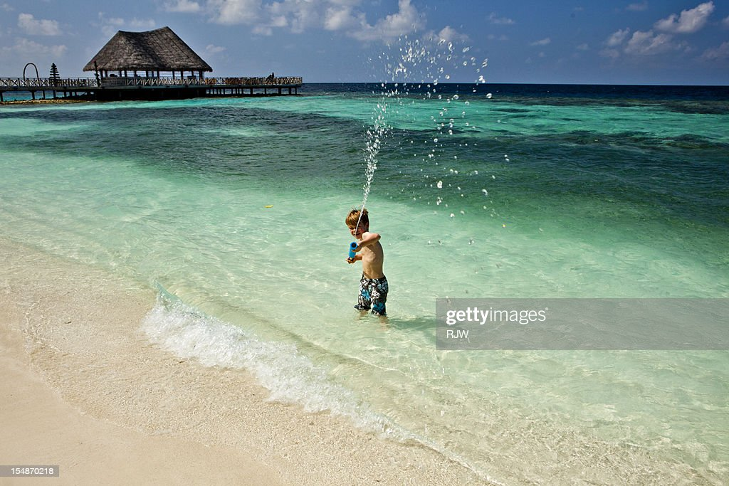 Boy in Ocean with Water Shooter : Stock Photo