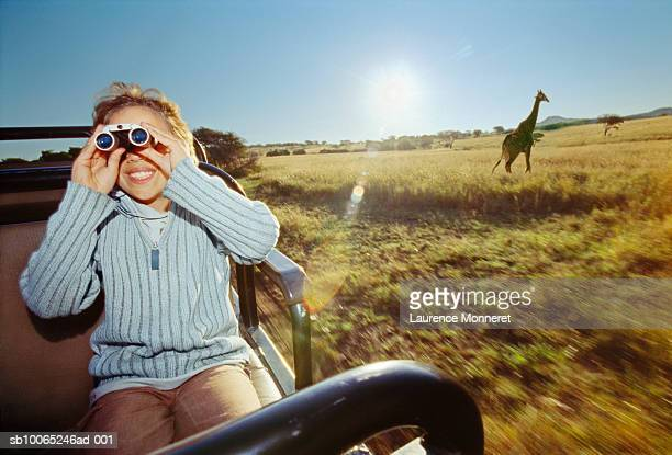 Boy (8-9) in off-road vehicle, looking through binoculars, giraffe in background