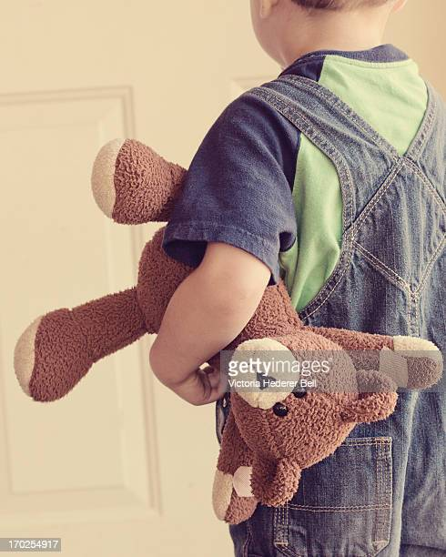 Boy in overalls carrying a teddy bear