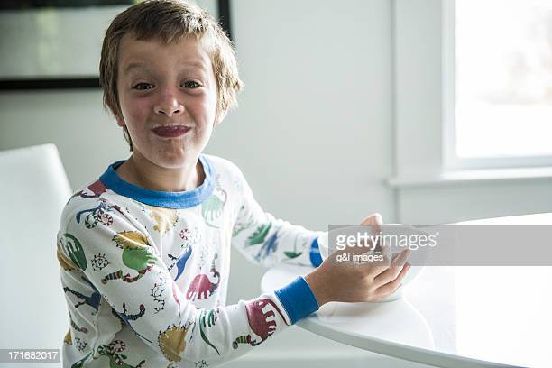 Boy in pajamas eating cereal