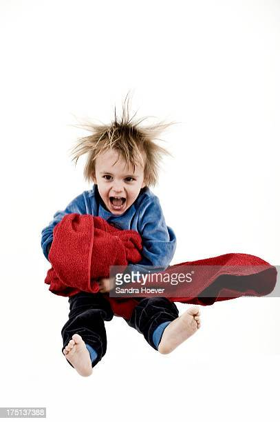 Boy (2-3) in pajamas jumping with blanket