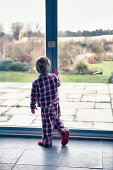 Boy in pajamas looking out window