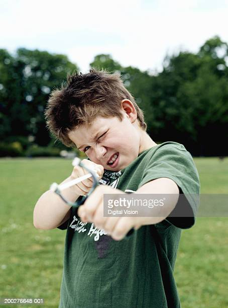 Boy (9-11) in park aiming catapult, portrait