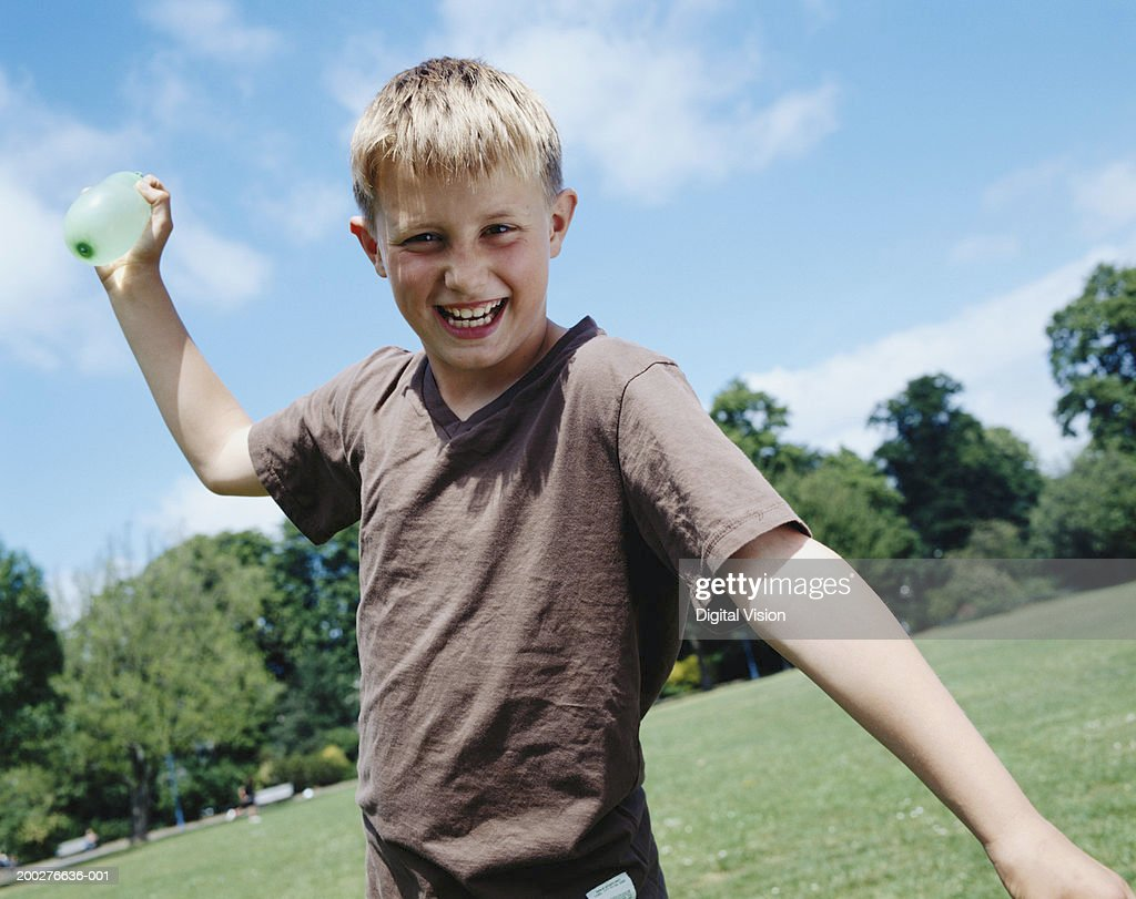 Boy (9-11) in park, aiming water bomb, smiling, portrait