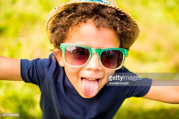 Boy in park sticking out tongue