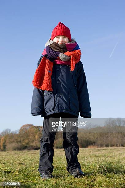 Boy in park wearing long knitted scarf, portrait